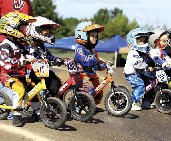 In this Sept. 8, 2012 photo provided by Strider Sports International, Inc., three year old children line up for the STRIDER race at the 2012 USA BMX Badger State Nationals held in Wisconsin Rapids, Wis. Gathered at the starting line, they look like mini versions of BMX racers, decked out in helmets, jerseys and protective gear with number plates on their tiny bikes. Once these toddlers get rolling, the difference between balance bike racing and the big boys becomes quickly apparent: No pedals, no brakes, just lots of little legs churning and loads of fun. (AP Photo/Strider Sports International, Inc.)