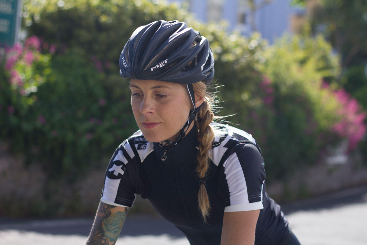 female cyclist jersey helmet thinking