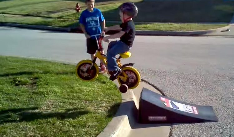 kid with helper wheels jupms ramp