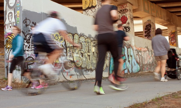 Atlanta, GA, USA - November 2, 2013:  Motion blur of several people exercising along a graffiti covered trail that is part of the Atlanta Beltline, a 22-mile long urban redevelopment project for the city of Atlanta that will eventually connect 45 intown neighborhoods.