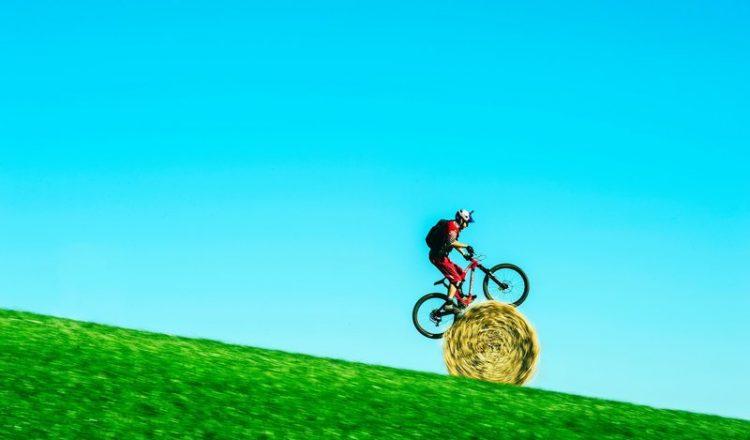 Danny MacAskill rolls down hill on hay bale